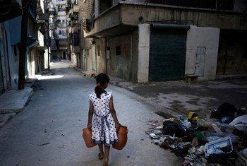 Criança carregando água em Aleppo, na Síria.