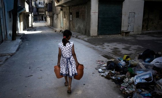 A girl, carrying jerrycans of water, walks past a pile of debris, on a street in Aleppo, Syria.