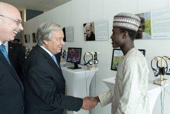 """O secretário-geral, António Guterres, saúda uma das vítimas do terrorismo com  experiência destacada na exibição multimídia """"Sobrevivendo ao Terrorismo: Vozes das Vítimas""""."""