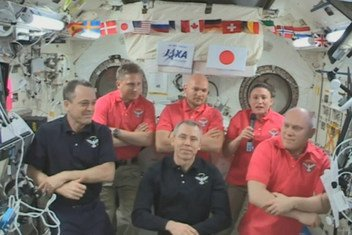 NASA astronaut Serena Auñon-Chancellor (right) with her fellow crew members of the International Space Station (ISS), on a live in-flight call to UNISPACE+50 on 20 June 2018.