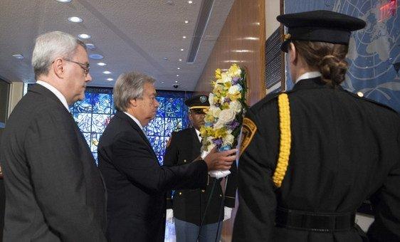 الأمين العام أنطونيو غوتيريش (وسط) يضع إكليلا من الزهورإحياء لذكرى من فقدوا أرواحهم في الهجوم الإرهابي على الأمم المتحدة في العراق.