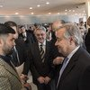 Secretary-General António Guterres speaks to terror victim Sayad Mushtaq Hussaini (left) at a multimedia exhibition to mark the first International Day of Remembrance of and Tribute to Victims of Terrorism, NY, August 2018.