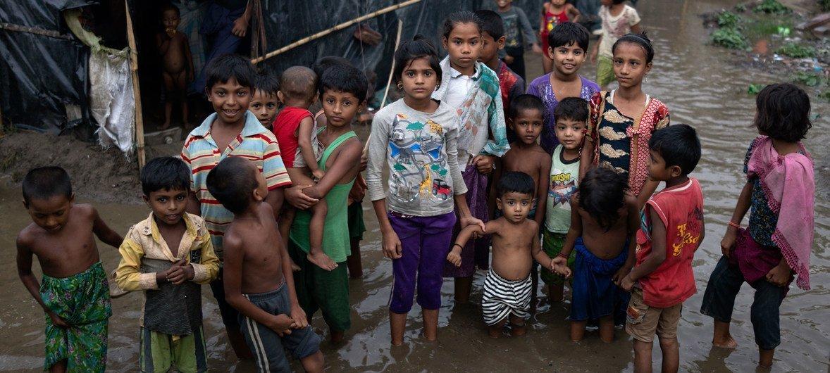 أطفال لاجئون من أبناء الروهينجا يقفون وسط مياه الفياضانات التي تحيط بملاجئ عائلاتهم في كوكس بازار ببنغلاديش