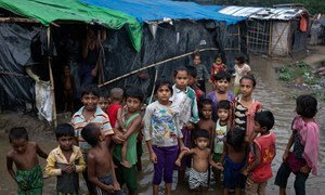 Pictured here, Rohingya refugee children wade through flood waters surrounding their families' shelters following an intense pre-monsoon storm in Shamlapur makeshift settlemen in Cox's Bazar district, Bangladesh.
