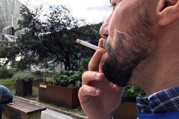 Un hombre fuma un cigarrillo en una zona designada para fumadores en la Sede de las Naciones Unidas en Nueva York, el 22 de agosto de 2018.