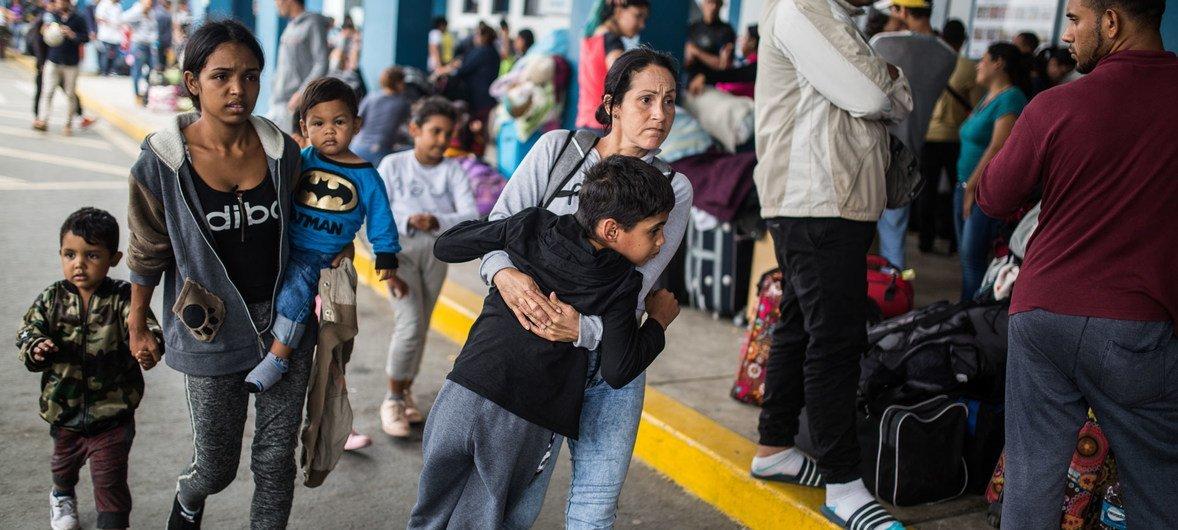 Una madre venezolana hace fila con su familia para entrar a Perú desde Ecuador.