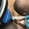 في بعض المواقع بجمهورية الكونغو الديمقراطية، يتعين على الأطفال غسل أياديهم قبل دخول المدارس.