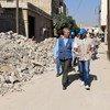 联合国难民事务高级专员格兰迪(图左)走过叙利亚东姑塔郊区杜马饱受战争创伤的街道。