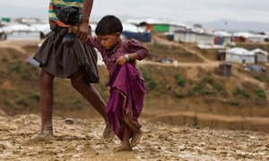 Two-year-old Rumana is led by a community worker as she and her family are relocated to a safer area of the Kutupalong-Balukhali camp, part of the refugee camp sheltering over 800,000 Rohingya refugees, Cox's Bazar, Bangladesh.