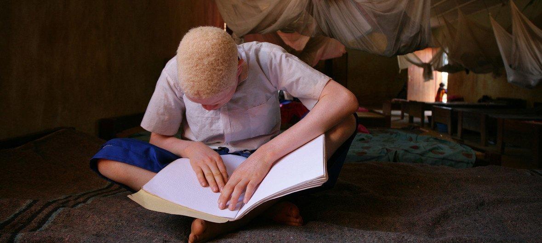 طفل كفيف يقرأ مستخدما لغة بريل في مدرسة ابتدائية للأطفال ذوي الإعاقة في بلدة موشي في تنزانيا.
