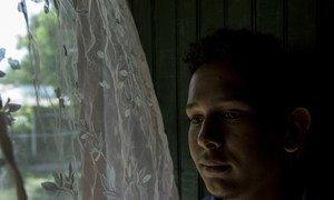 Victor Fernando, 17 ans, se tient près de la fenêtre de son domicile de Villanueva, au Honduras. Il a été victime d'intimidation à l'école concernant son orientation sexuelle. Depuis que l'intimidation a commencé, ses notes ont chuté.