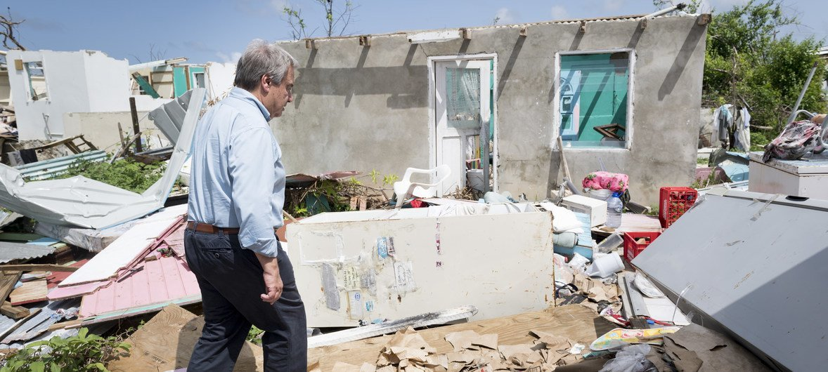 In 2017, Secretary-General António Guterres walks through a neighbourhood destroyed by back-to-back hurricanes in Codrington town, Antigua and Barbuda. He visited the country to survey the devastation and offer support from the Organization.
