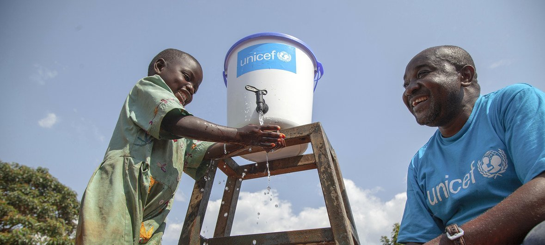 Un employé de l'UNICEF parle à une petite fille qui se lave les mains pour prévenir la propagation du virus Ebola au Nord-Kivu, en République démocratique du Congo (RDC).