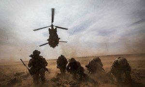 Membros da equipe médica canadense se protegem contra a poeira de um helicóptero que decola durante um exercício de evacuação médica.