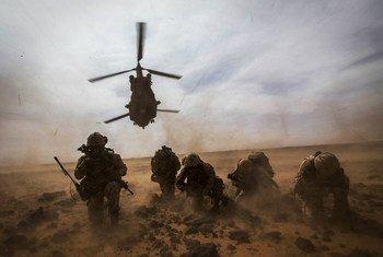 Un hélicoptère canadien CH-147 Chinook décolle alors que les Casques bleus canadiens de la MINUSMA se protègent de la poussière lors d'un exercice d'évacuation médicale près de Gao au Mali.