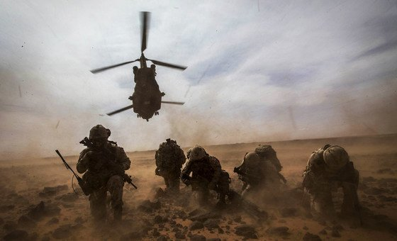 A CH-147 Chinook helicopter takes off while Canadian UN peacekeepers protect themselves from dust during a medical evacuation exercise around Gao in Mali.