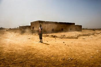 Un jeune garçon se tient sur la route alors que les vents et le sable s'accumulent dans la banlieue de Kaédi, en Mauritanie.