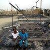 12 साल की चुबाट (दाएं) अपनी सहेली के साथ जल कर खंडहर हो चुके स्कूल में बैठी है
