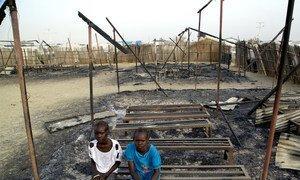 Chubat, de 12 anos, à direita, com uma amiga nas ruinas da sua escola, em Malakal, no Sudão do Sul.