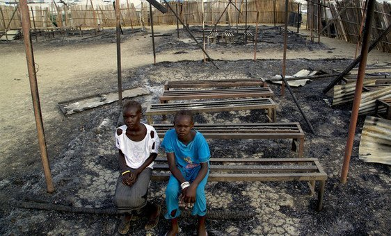 On 3 March 2016, Chubat (right), 12, sits with her friend in the burned ruins of her school in Malakal, South Sudan.