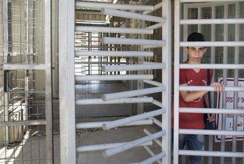 الطفل الفلسطيني مروان، 14 عاما، يعبر نقطة تفتيش تقع في نهاية الشارع الذي يسكن فيه. يمر مروان بهذه النقطة في طريقه إلى المدرسة في مدينة الخليل.