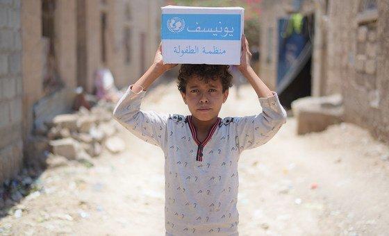 2018年9月,也门萨那北部的一个居民区,一名12岁的男孩拿着一箱由联合国提供的肥皂。