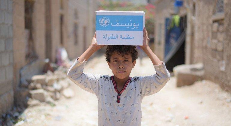 Un niño de 12 años lleva una caja con jabón suministrado por las Naciones Unidas en el barrio de Bani Harith de Sana'a, en Yemen.