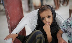 A child waits as UNICEF-supported emergency humanitarian supplies are distributed in Hudaydah, Yemen in June 2018.