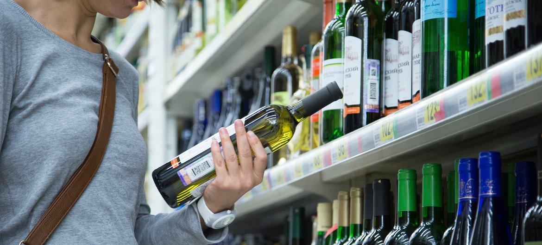 Una mujer observa una botella de vino en un supermercado de Moscú.