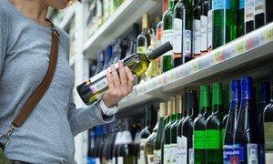 Женщина выбирает алкогольные напитки в супермаркете Москвы, Россия