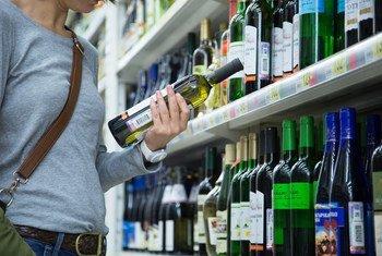 Женщина выбирает алкогольные напитки в супермаркете.