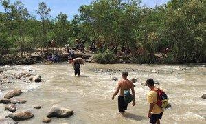"""Las """"trochas"""" son cruces ilegales en la frontera entre Colombia y Venezuela. En esta imagen, venezolanos cruzan un río cerca de Cúcuta, en Colombia en septiembre de 2018."""