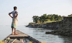 Un niño observa la orilla desde un barco cerca de Sirajganj, una comunidad afectada por la grave sequía que ha dejado a muchos desplazados. Sirajganj, Bangladesh