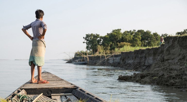 A boy watches the shore from a boat near Sirajganj, a community affected by severe erosion that has left many displaced. Sirajganj, Bangladesh. October 2016