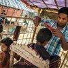 2017年12月,28岁的缅甸难民、理发师纳吉布拉(Najibullah)在孟加拉国难民营的理发店里为顾客剪头发头发。