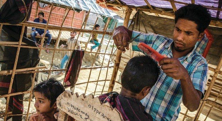Najibullah, de 28 años, corta el pelo a un cliente en su barbería del campo de Moynerghona, en Bangladesh.