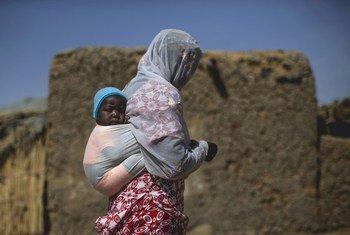 Una mujer y su hijo, desplazados por la violencia en la ciudad maliense de Tombuctú y sus alrededores, caminan por una aldea de desplazados internos en Mopti, donde viven unas 40 familias.