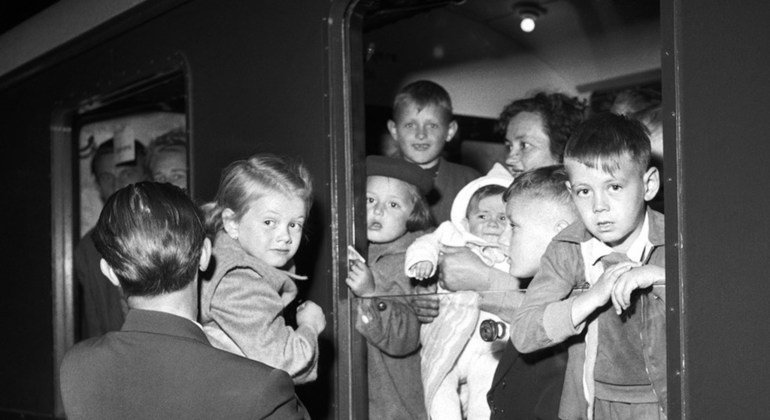 Refugees on their way to Sweden are shown arriving by train in Copenhagen.  These refugees participated in a special resettlement program for refugee families with one or more members with physical handicaps.
