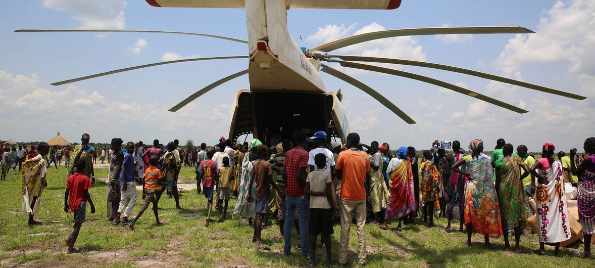 Local volunteers unload the supplies from the back of the helicopter of a UNICEF Rapid Response Mission (RRM) in New Fangkak, South Sudan on 21 July 2018.  The supplies include tetanus vaccine and polio drops, plumpy nut, child protection items, education kits and WASH kits.