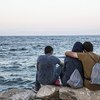 Migrants look out to sea in Lesvos, Greece (file).