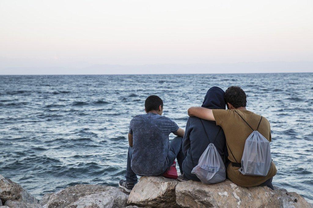 Des migrants regardent la mer sur l'île de Lesbos, en Grèce.