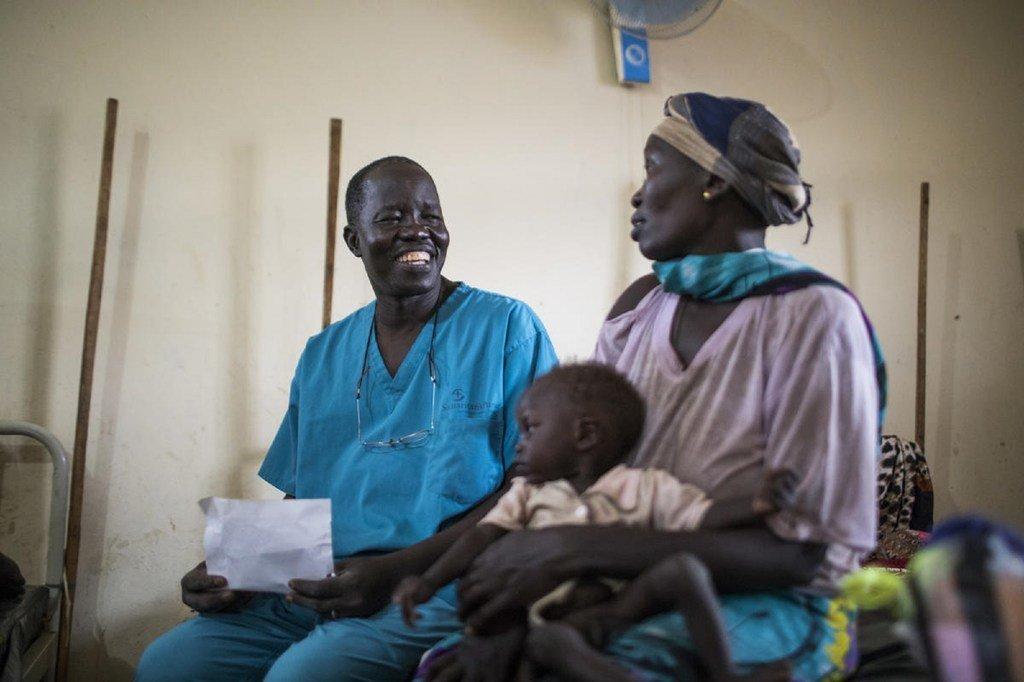 阿塔尔医生与来自苏丹的一位难民妇女和她营养不良的儿子在本杰镇的医院里交谈。