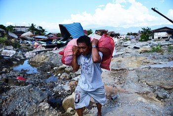 Residents carry possessions salvaged from the rubble of homes in West Palu, Central Sulawesi, after the earthquake and tsunami that struck Sulawesi on 28 September 2018.