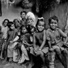 An elderly couple surrounded by their grandchildren in the Banjara tribal community near Hyderabad. 1981.