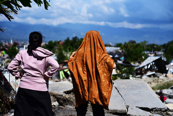 People look at destroyed buildings in West Palu, central Sulawesi, in the aftermath of an earthquake and tsunami that struck the island in September 2018.