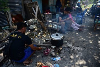 A resident cooks in front of their house with simple equipment because they are still worried that there will be aftershocks in East Lolu, Palu City, Central Sulawesi, Indonesia (2 October).