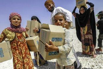 Une famille reçoit des vêtements de l'UNICEF dans le camp de fortune de Mabrouka, en Syrie, en août 2018.