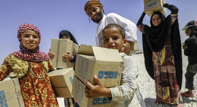Una familia recibe una donación de UNICEF en un campamento de desplazados internos en Mabrouka, en la provincia de al-Hasakah, Siria.