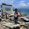 A ten-year-old child stands in front of his home, which was destroyed by the tsunami in Central Sulawesi, Indonesia.