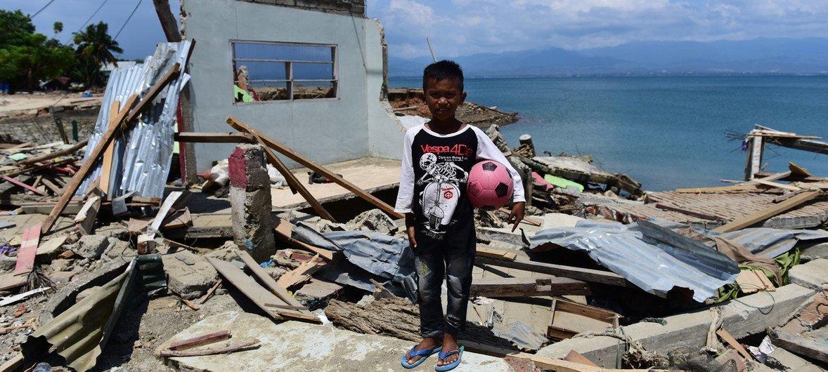 10岁的里多·萨普特拉站在他在印度尼西亚中苏拉威西省东加拉县被海啸摧毁的房子前( 10月3日)。